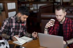 Funcionamiento en línea que bloguea de los hombres de negocios jovenes por los ordenadores portátiles en café fotografía de archivo