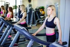 Funcionamiento en la rueda de ardilla en gimnasio o el club de fitness - grupo de mujeres que hacen ejercicios cardiios Imagen de archivo libre de regalías