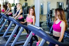 Funcionamiento en la rueda de ardilla en gimnasio o el club de fitness - grupo de mujeres que hacen ejercicios cardiios Fotos de archivo