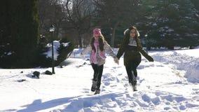 Funcionamiento feliz de la hija de la madre y del bebé de la familia, paseo que juega en invierno al aire libre en la nieve almacen de video