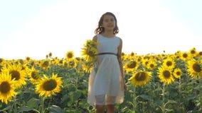 Funcionamiento feliz de la niña feliz libremente a través del campo con los girasoles vídeo de la cámara lenta girasol grande que almacen de metraje de vídeo