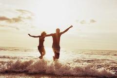 Funcionamiento feliz de la playa de la puesta del sol de los pares fotos de archivo