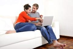 Funcionamiento feliz de los pares o compras en línea en su ordenador portátil en el sofá Fotografía de archivo