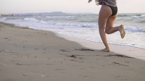 Funcionamiento femenino, activando descalzo en la arena de la playa del océano en la salida del sol Imagenes de archivo