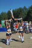 Funcionamiento festivo de muchachas hermosas jovenes de animar el VÉRTIGO del grupo de ayuda de los atletas (vértigos) Foto de archivo libre de regalías