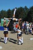 Funcionamiento festivo de muchachas hermosas jovenes de animar el VÉRTIGO del grupo de ayuda de los atletas (vértigos) Imagen de archivo libre de regalías