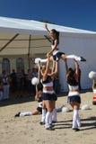 Funcionamiento festivo de muchachas hermosas jovenes de animar el VÉRTIGO del grupo de ayuda de los atletas (vértigos) Imágenes de archivo libres de regalías