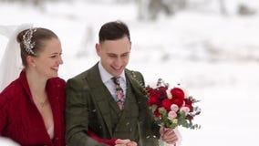 Funcionamiento joven de los pares de la boda, divirtiéndose que celebra las manos en el pueblo de la estación de esquí con las ca