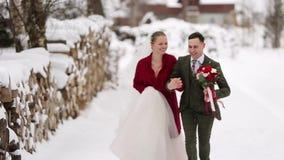 Funcionamiento joven de los pares de la boda, divirtiéndose que celebra las manos en el pueblo de la estación de esquí con las ca almacen de video