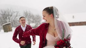 Funcionamiento joven de los pares de la boda, divirtiéndose que celebra las manos en el pueblo de la estación de esquí con las ca almacen de metraje de vídeo