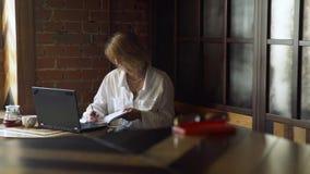 Funcionamiento maduro de la mujer mientras que se sienta en cafetería almacen de metraje de vídeo
