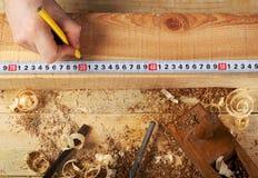 Funcionamiento, martillo, metro y destornillador del carpintero en fondo de la construcción Imagenes de archivo
