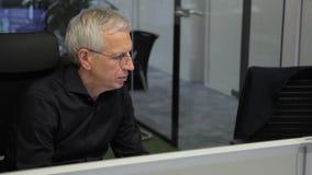 Funcionamiento mayor del jefe mientras que se sienta en el ordenador en oficina moderna metrajes
