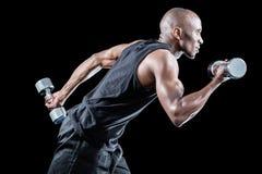 Funcionamiento muscular del hombre mientras que lleva a cabo pesa de gimnasia Imagenes de archivo