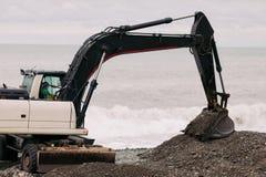 Funcionamiento negro pesado del excavador en la playa imagen de archivo libre de regalías