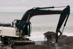 Funcionamiento negro pesado del excavador en la playa foto de archivo libre de regalías