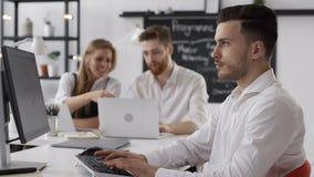 Funcionamiento o planeamiento atractivo acertado del hombre de negocios en oficina creativa de moda
