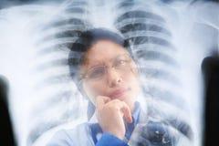 Funcionamiento ocupado del doctor de sexo femenino asiático en resultado de la radiografía Imágenes de archivo libres de regalías