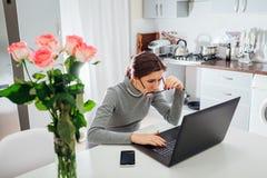 Funcionamiento que habla de la mujer en el ordenador portátil en cocina moderna Freelancer irritado enojado que mira fijamente la foto de archivo libre de regalías