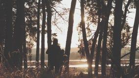 Funcionamiento síncrono de dos corredores masculinos jovenes en rastro del bosque del otoño Ejercicios de funcionamiento de la ge almacen de metraje de vídeo