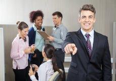 Funcionamiento sonriente de Pointing While Employees del encargado Foto de archivo