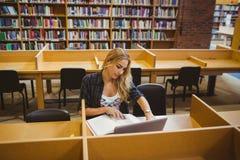 Funcionamiento sonriente del estudiante mientras que usa su ordenador portátil fotos de archivo libres de regalías