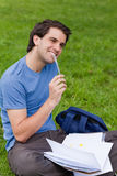 Funcionamiento sonriente joven del hombre mientras que se sienta en la hierba Fotos de archivo libres de regalías