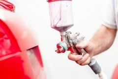 Funcionamiento y pintura del ingeniero automotriz en cuerpo de un coche Imagen de archivo libre de regalías