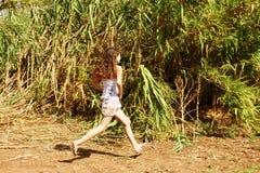 Funcionamientos adolescentes de la muchacha a través de un campo fotos de archivo