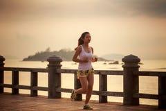 funcionamientos asiáticos de la muchacha en la salida del sol Fotos de archivo libres de regalías