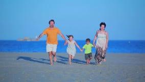Funcionamientos de la familia al mar en la playa metrajes