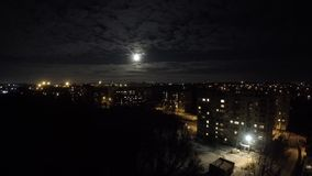 Funcionamientos de la luna de Timelapse detrás de las nubes sobre pueblo metrajes