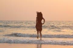 Funcionamientos de la muchacha a lo largo de la playa en la puesta del sol Fotografía de archivo libre de regalías
