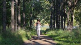 Funcionamientos de la muchacha a lo largo de un callejón sombrío del Forest Green Mujer joven que activa en el parque almacen de video