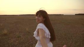 Funcionamientos de la muchacha a trav?s del campo que lleva a cabo la mano de su hombre y risas queridos C?mara lenta feliz en fu almacen de metraje de vídeo