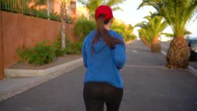 Funcionamientos de la mujer abajo de la calle entre las palmeras en la puesta del sol, visión trasera Forma de vida activa sana almacen de video