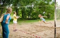 Funcionamientos de la mujer que intentan rechazar volante que vuela durante competencias aficionadas del tenis de la playa imagen de archivo libre de regalías