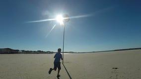 Funcionamientos del muchacho a lo largo de la orilla para la pelota de playa metrajes