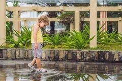 Funcionamientos del niño pequeño a través de un charco Verano al aire libre fotografía de archivo libre de regalías
