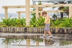 Funcionamientos del niño pequeño a través de un charco Verano al aire libre imágenes de archivo libres de regalías