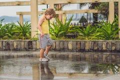 Funcionamientos del niño pequeño a través de un charco Verano al aire libre foto de archivo libre de regalías