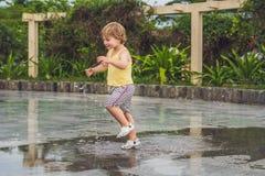 Funcionamientos del niño pequeño a través de un charco Verano al aire libre foto de archivo