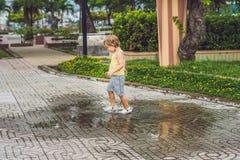 Funcionamientos del niño pequeño a través de un charco Verano al aire libre imagen de archivo