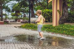 Funcionamientos del niño pequeño a través de un charco Verano al aire libre imagenes de archivo