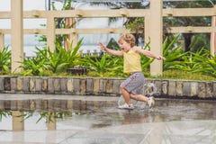 Funcionamientos del niño pequeño a través de un charco Verano al aire libre fotografía de archivo