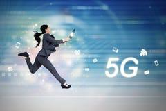 funcionamientos del símbolo y de la mujer de la red 5G con el ordenador portátil imagenes de archivo
