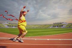 Funcionamientos divertidos gordos del hombre al final en pista en el estadio foto de archivo