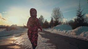 Funcionamientos felices de la niña en las trayectorias de la nieve en el parque almacen de metraje de vídeo