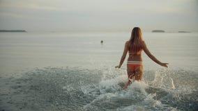 Funcionamientos hermosos de la muchacha en el agua Espray dispersado La mujer joven delgada corre por la tarde en la puesta del s almacen de metraje de vídeo