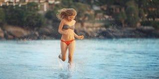 Funcionamientos hermosos de la muchacha a lo largo de la playa imagen de archivo
